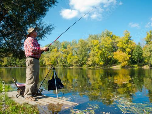 Fotografie, Obraz  Senior fisherman catches a fish