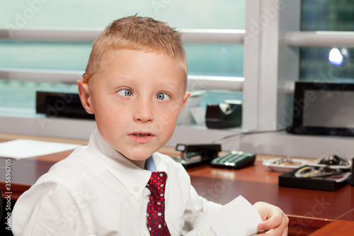 Photo  Cute boy with goofy face in business attire in an office