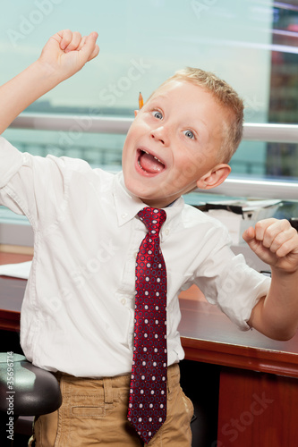 Cute boy with goofy face in business attire in an office Canvas Print