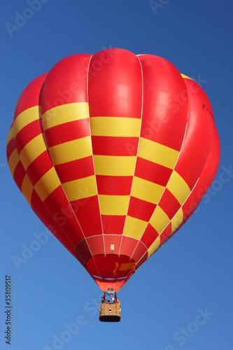In de dag Ballon Mongolfière rouge et jaune dans un grand ciel bleu