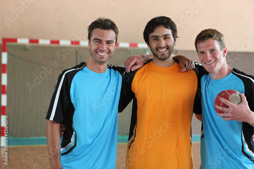 Fotografiet  Three grinning footballers in front of goal