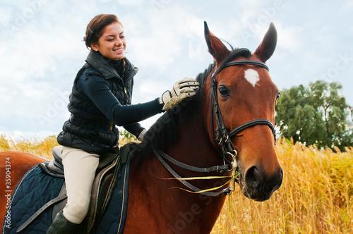 Vászonkép Pretty girl riding horse front of reed