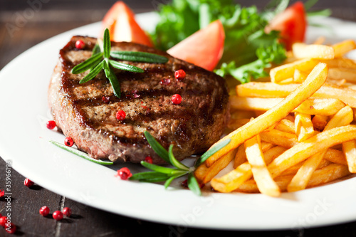Aluminium Prints Steakhouse Grilled rustic steak with french fries