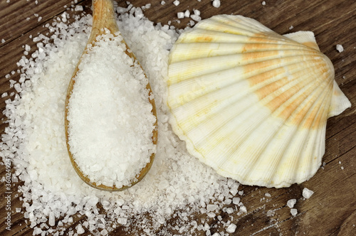 Fotografija  Coarse sea salt on a wooden table with spoon and scallop shell