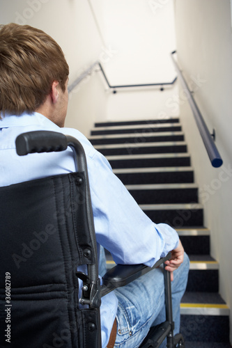 Fotografie, Obraz  Man in wheelchair at foot of stairs