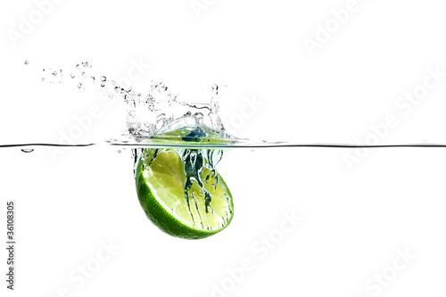Halbe Limette fällt spritzend ins Wasser