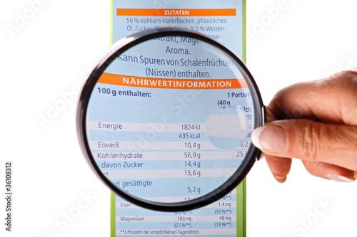 Fotografie, Obraz  Verbraucherin nimmt Nährwertinformationen unter die Lupe