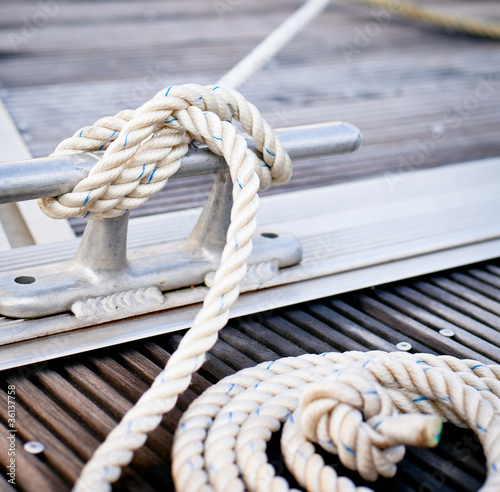 White mooring rope tied around steel anchor on boat or ship. Fototapeta