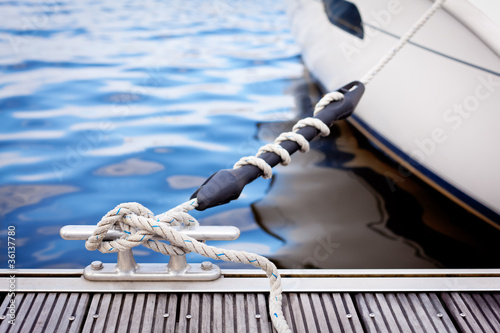 Fotografia A white yacht moored with a line tied around a metal fixing