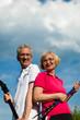 Glückliches älteres Paar beim Nordic Walking im Sommer