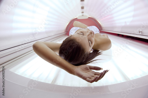 Photo Beautiful young woman tanning in solarium