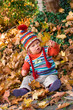 baby is sitting in autumn foliage