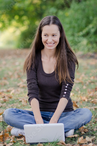 Fototapety, obrazy: Girl sitting on the grass working on laptop at the park
