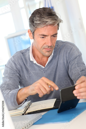 Man working in office on calculator - 36272304