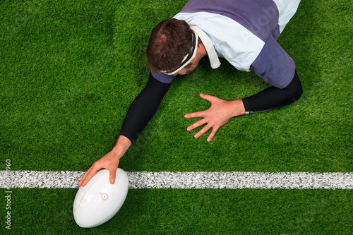 Photo  Rugby player scoring a try with one hand on the ball