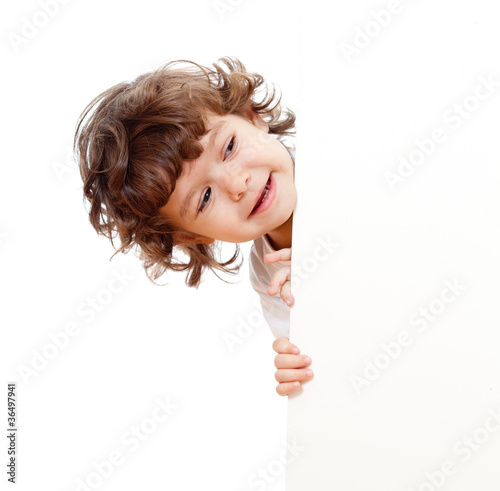 Vászonkép Curly funny child face holding blank advertising banner