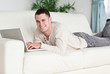 Smiling man lying on a sofa with a laptop