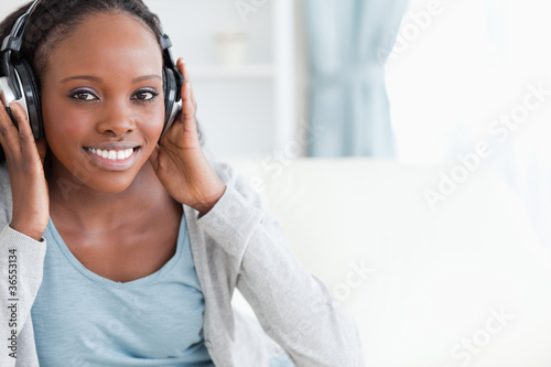 Fototapety, obrazy: Close up of woman listening to music on couch
