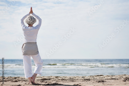 Spoed Foto op Canvas School de yoga aktive Seniorin macht Yoga am Strand