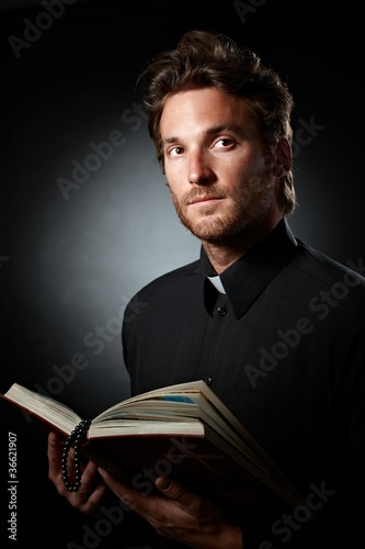 Portrait of young priest with Bible. Fototapeta
