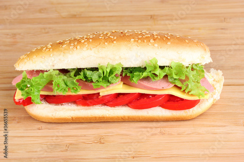 Sandwich with sausage, cheese and tomatoes on wooden background