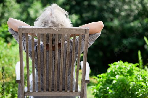 Fotografía  grauhaarige Frau entspannt im Garten