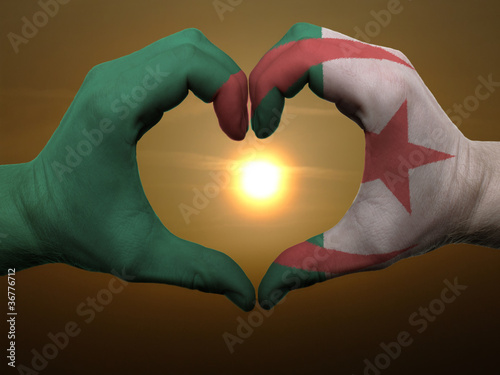 Papiers peints Algérie Heart and love gesture by hands colored in algeria flag during b