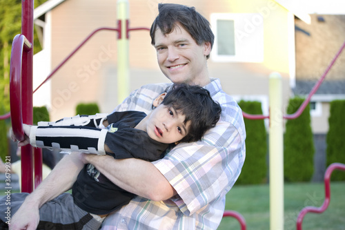 Valokuva  Father helping disabled son to play at playground