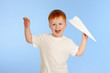 Adorable red-haired boy with paper plane model on blue backgroun