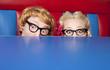 Leinwanddruck Bild - Nerdy couple hiding behind a table