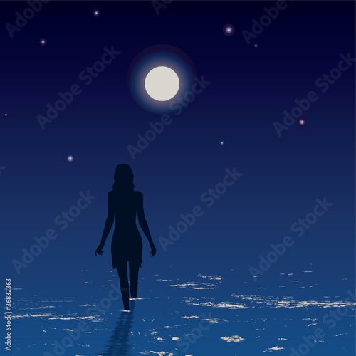 Silhouette of young woman walking on a sea