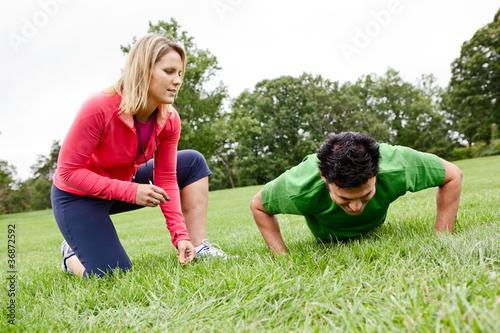 Trainer coaching man doing push ups