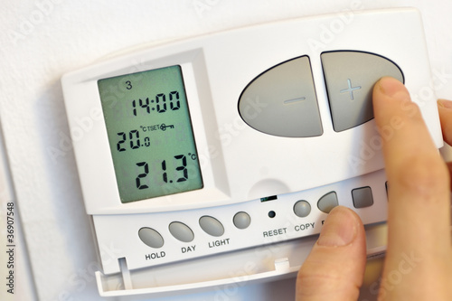 Photo  hand pressing button on digital thermostat