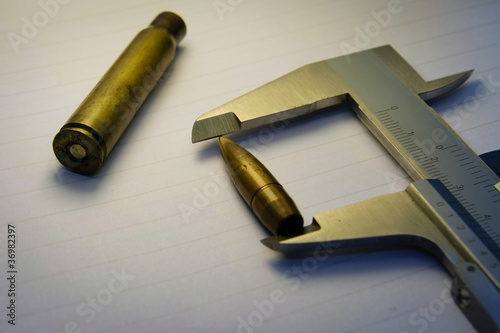фотография  Measuring a bullet with Vernier on white background