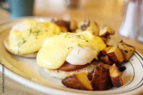 Delicious eggs benedict with seasoned potatoes for breakfast. Wallpaper Mural