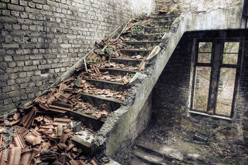 Tuinposter Rudnes Collapsed roof tiles on a staircase in a derelict building