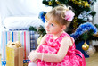 A little girl in a smart dress near the Christmas Tree/