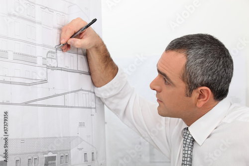 Fototapeta Architect working on a blueprint