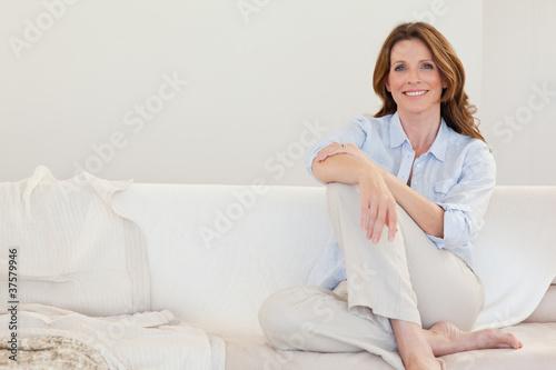 Obraz na plátně Smiling mature woman sitting on sofa