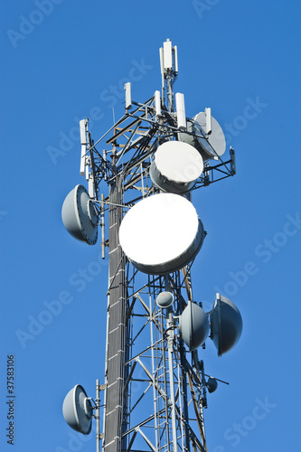Fotografie, Tablou  Cell tower and radio antenna in trees against a blue sky