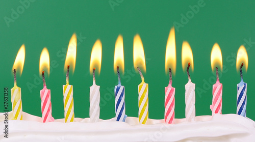 10 lit birthday candles in bright colors with green background buy
