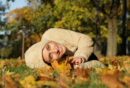 Fotografering  Attractive young woman against autumn leaves