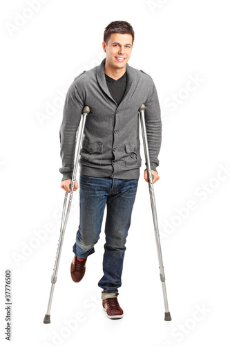 Full length portrait of an injured young man on crutches Canvas Print