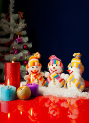 Three snowmen and burning candles over the blue background