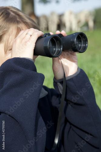 Valokuva  Looking through binoculars