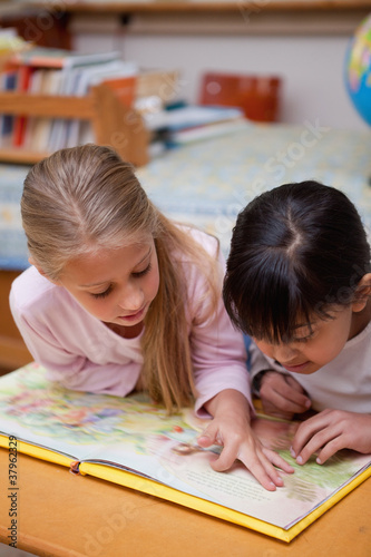 Foto op Plexiglas Wand Portrait of schoolgirls reading a fairy tale