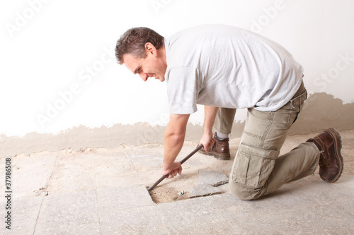 Fotografie, Obraz  Manual worker disassembling old floor tiles