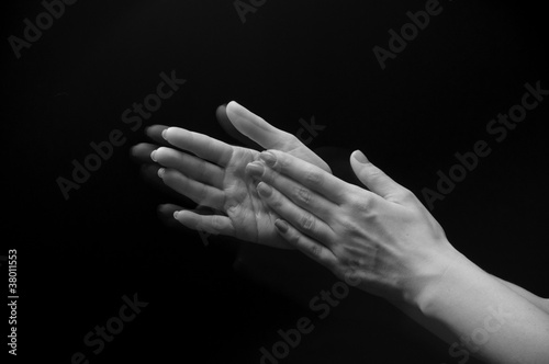 Fotografía  Female hands clapping on black, side-view