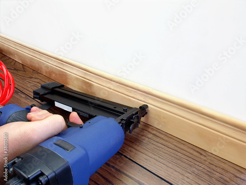 Male hand with carpenter tool installing baseboard Canvas Print