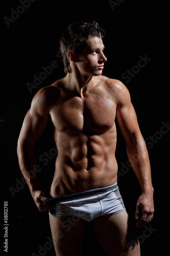 Photographie  The muscular young naked sexy boy takes off her underwear